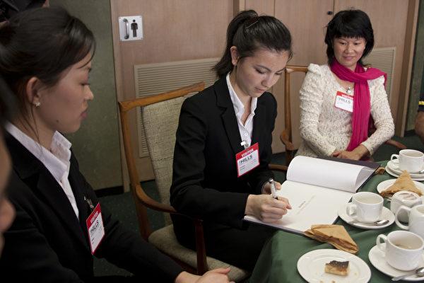 孙兰兰在赠送给山区郡郡长Michelle Byrne的神韵画册上签名(摄影:袁丽/大纪元)