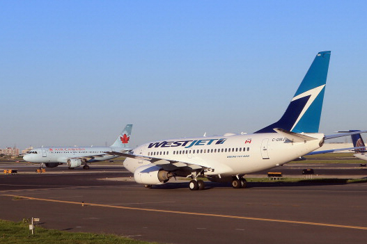 TORONTO, ON - AUGUST 28:  A WestJet flight and an Air Canada flight cross paths on a runway at the Lester B. Pearson airport as photographed from an airplane on August 28, 2012 in Toronto, Canada.  (Photo by Bruce Bennett/Getty Images)