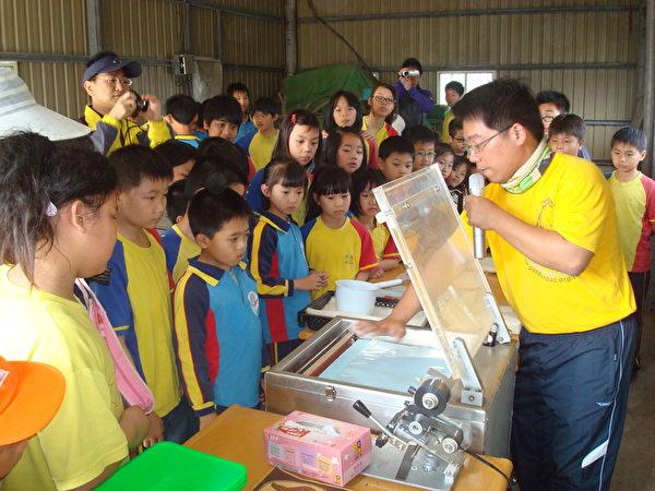 台湾永续联盟理事长张添顺向学生说明稻米真空包装的操作过程。(摄影:黄丽医/大纪元)
