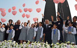 """镇南国小学生手持象征""""爱、希望、和平228""""的气球,将希望气球放飞升空。(县府提供)"""