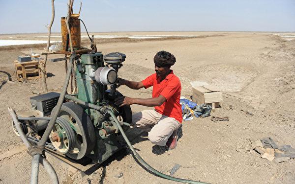 2013年3月7日,在离艾哈迈达巴德约240公里处的桑德尔布尔(Santalpur)地区的小兰恩的卡奇(Little Rann of Kutch),一名印度的盐沼工人正在检查水泵。成千上万的盐工缺乏基本的设施和他们孩子的前途也是个未知数,因为许多学校都没有足够的和有经验的教职人员。 (Sam PANTHAKY/AFP)