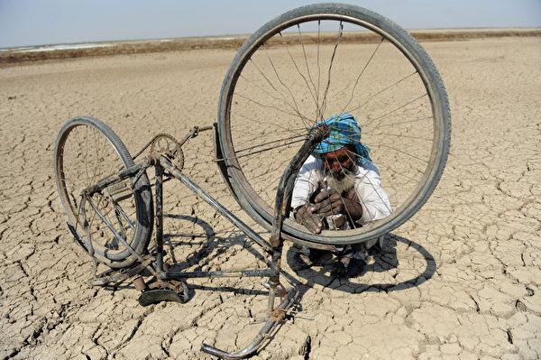 2013年3月7日,在离艾哈迈达巴德约240公里处的桑德尔布尔(Santalpur)地区的小兰恩的卡奇(Little Rann of Kutch),一名印度的盐沼工人正在修理他的脚车。成千上万的盐工缺乏基本的设施和他们孩子的前途也是个未知数,因为许多学校都没有足够的和有经验的教职人员。 (Sam PANTHAKY/AFP)