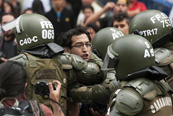 2013年3月7日,在圣地亚哥(Santiago),防暴警察逮捕了抗议的学生,学生要求智利总统塞巴斯蒂安·皮涅拉(Sebastian Pinera)领导的政府改善公共教育体系。 (Claudio SANTANA/AFP)