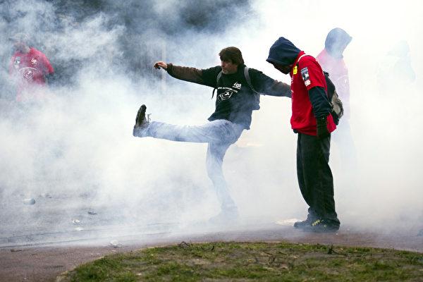 2013年3月7日,在固特异(Goodyear)美国轮胎和橡胶公司于巴黎(Paris)西部郊区的Rueil-Malmaison法国总部前面在开董事会会议时,抗议中的固特异法国工人面对防暴警察的催泪瓦斯的伺候。固特异在2013年1月宣布,将在2014年年底,关闭在法国北部的亚眠(Amiens)的工厂。工厂的员工有1250人。由于对其产品的需求的减少,固特异公司的工厂去年遭受的损失约有50亿欧元(67亿美元)。 (LIONEL BONAVENTURE/AFP)