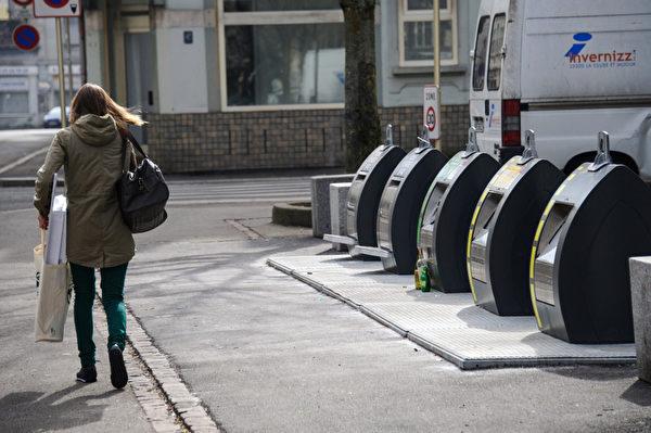 2013年3月7日,在法国的米卢斯(Mulhouse),一名妇女经过用来做垃圾分类的废物箱。 (SEBASTIEN BOZON/AFP)