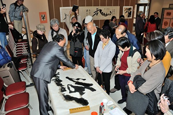 王建中在3月9日的书画展开幕式上现场为来宾挥毫。(摄影:曹景哲/大纪元)