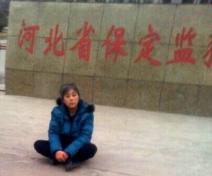 悲愤的郑祥星妻子孙素云坐在保定监狱外冰冷的水泥地上,向社会呼救。(图片来源:明慧网)