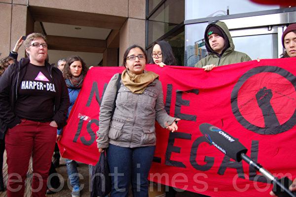"""3月14日,部分被抓非法外劳的家属与支持者,在温哥华市中心联邦移民难民局大楼前抗议,要求释放这些外劳。前面的是""""没有人是非法的""""组织发言人沃利亚。 (摄影:邱晨/大纪元)"""