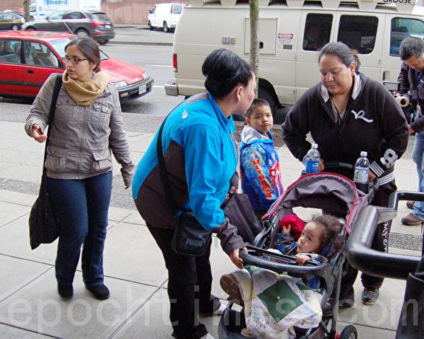 一女士琼瑟夫(右一着黑衣女子)携带两名年幼子女,也来到联邦移民难民局大楼前抗议。(摄影:邱晨/大纪元)