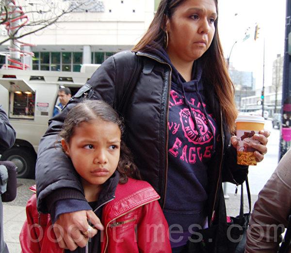 一个被抓的外劳的妻子汤普森(Diana Thompson)和女儿在联邦移民难民局大楼前抗议。(摄影:邱晨/大纪元)