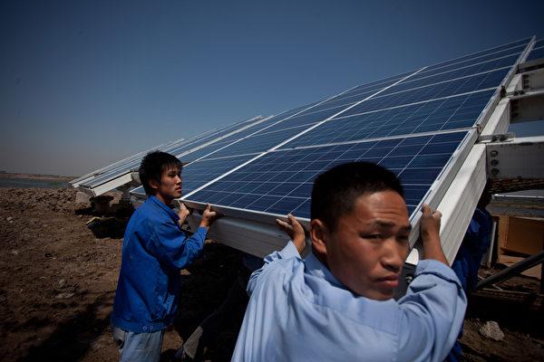目前中國的五大生產商全都經營慘淡,而且債務情況嚴重。圖為天津工人正在為中新合資企業安裝太陽能面板。 (AFP/GettyImages)