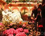 图为在花展大厅中用花装饰的大象旁,游人用相机为自己喜欢的花卉留影。(摄影:杜国辉/大纪元)