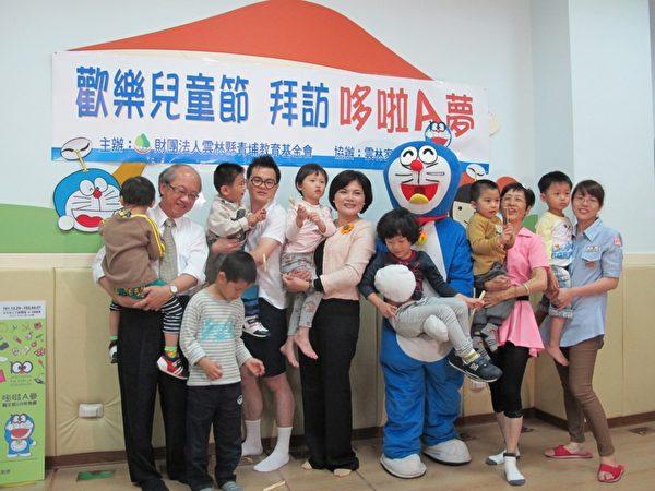 张丽善和家扶人员抱着孩子们开心的一起合影。(摄影:廖素贞/大纪元)
