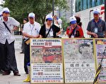 图为台北101大楼前,驻足观看法轮功真相展板的中国观光客。(明慧网)