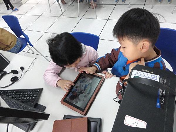 小朋友使用平板玩游戏,聚精会神玩上瘾。(摄影:丁弘毅/大纪元)