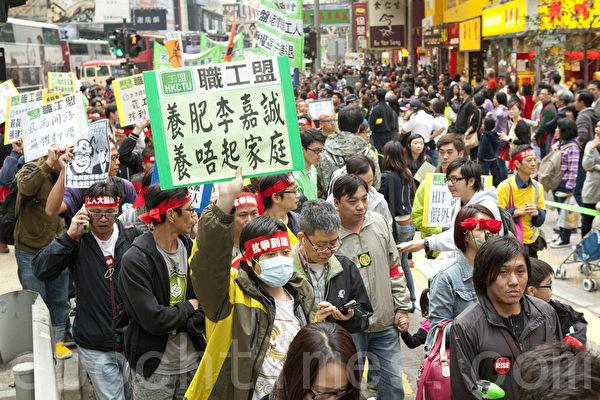 4月7日,香港货柜码头工人罢工工潮进入十一日,工友和支持罢工的家属和市民下午在维园集会,并游行到长江中心及政府总部,表达诉求和抗争到最后的决心。(摄影:余钢/大纪元)