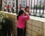 被禁止上學的張安妮隔牆與牆內同學說話 (網友提供)