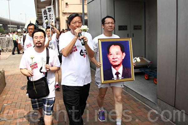 長跑人士手持胡耀邦遺像和民主女神像前往中聯辦。(攝影:潘在殊/大紀元)