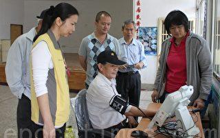 神木村村長鍾桂南試用遠距照護系統的生理量測設備。(攝影:林萌騫/大紀元)