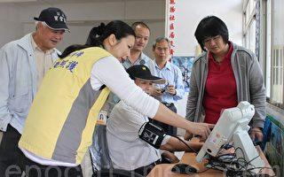 竹山秀傳遠距照護人員為民眾說明生理量測機器螢幕上的健康數據。(攝影:林萌騫/大紀元)
