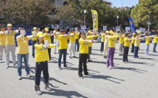 4月21日,旧金山法轮功学员在中国城举行系列讲真相活动,纪念四二五和平上访。图为法轮功学员在花园角集会上展示法轮功功法动作。(摄影:马有志/大纪元)
