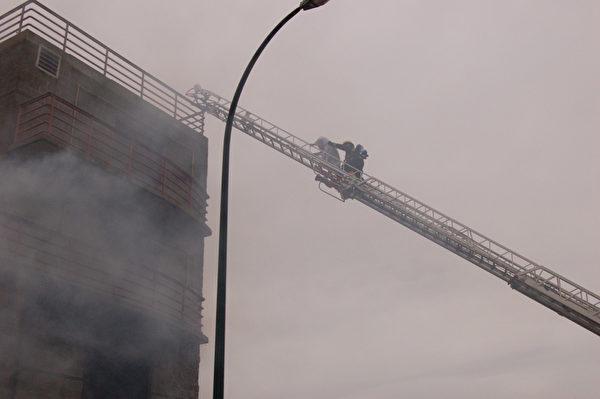 图:4月26日,温哥华消防队员靴子夏令营现场演习救火。图为培训基地的石头房屋室内着火,救援人员将屋顶妇女救下来。(摄影:邱晨/大纪元)