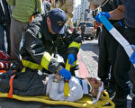 4月28日,在Jackson街上一位西人老者突然摔倒不起,附近的退党服务中心义工找来消防队员急救。(摄影:曹景哲/大纪元)
