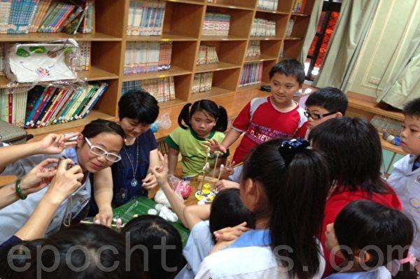 配合主题书展于美龄老师示范捏面人技巧教学,大批小朋友争相学习。(摄影:宋顺澈/大纪元)