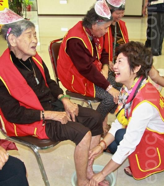 96歲的鍾徐秀妹給蔡麗卿洗腳時很享受,邊洗還邊唱「採茶歌」。(攝影:許享富 /大紀元)