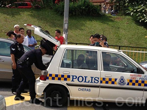 警察看见大批群众发怒大声叫嚣,不得不将这名被人怀疑的选民载走。(摄影:张建浩/大纪元)
