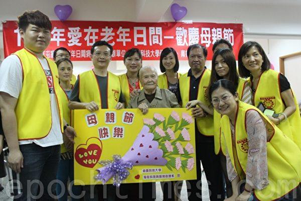 南開科大福祉系所師生將超大康乃馨卡片獻給所有老年日間病房的長者,由96高齡的李日阿嬤代表接受。(攝影:林萌騫/大紀元)