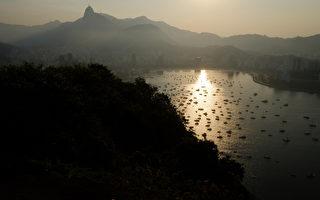 巴西里约热内卢,博塔弗戈湾与科尔科瓦山的夕阳,游艇散布在海岸和山銮之间。摄于5月5日。(CHRISTOPHE SIMON/AFP)