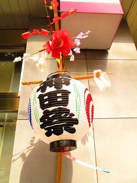 各家户门廊下张挂神田祭节庆的装饰灯笼;祭典适逢五月牡丹花盛开季节,灯笼上装饰着牡丹同时传达季节的信息。