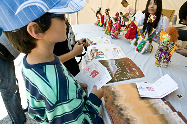 """孩子们拿着文化节""""护照""""到各个摊位收集印章可领奖。(摄影:曹景哲/大纪元)"""
