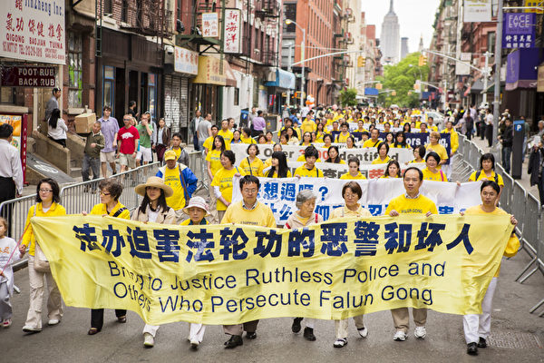 5月18日的纽约曼哈顿,来自世界各地的法轮功学员举行庆祝法轮大法弘传21周年大游行。图为游行队伍第二主题《千古蒙冤 制止迫害》方阵,要求法办迫害法轮功的元凶。(摄影:爱德华/大纪元)