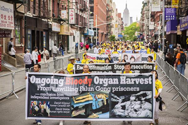 5月18日的纽约曼哈顿,来自世界各地的法轮功学员举行庆祝法轮大法弘传21周年大游行。图为游行队伍第二主题《千古蒙冤 制止迫害》方阵,揭露中共活摘器官暴行的横幅。(摄影:爱德华/大纪元)