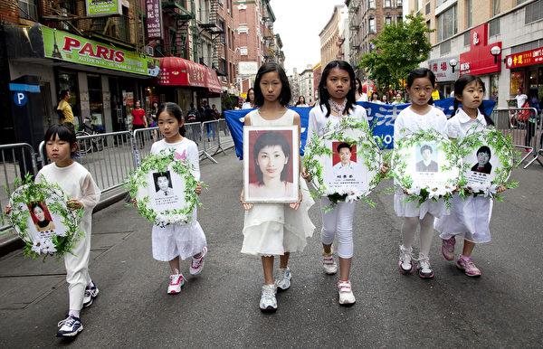 5月18日的纽约曼哈顿,来自世界各地的法轮功学员举行庆祝法轮大法弘传21周年大游行。图为法轮大法小弟子持被迫害致死的法轮功学员的照片表达悼念。(摄影:季媛/大纪元)