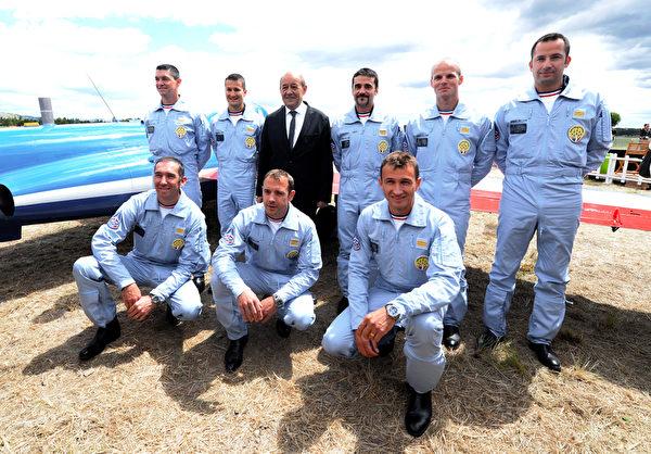 """2013年5月25日,法国""""法兰西巡逻兵""""进行特技飞行演出,庆祝""""巡逻兵""""成立 60周年。图为法国国防部长让- 伊夫• 勒排液(后排,左三)和""""法兰西巡逻兵""""飞行员。(GERARD JULIEN/AFP)"""