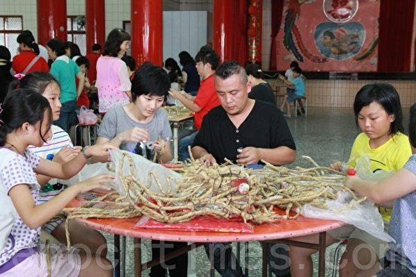 草龙制作师傅钟邦虎(左3)用稻草指导乡亲制作云火龙。(摄影:许享富/大纪元)