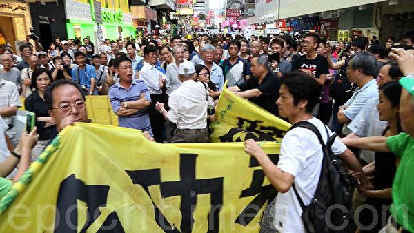 憤怒的市民採取行動,要把惡黨團夥遮擋法輪功真相點的橫幅扯開。(攝影:潘在殊/大紀元)