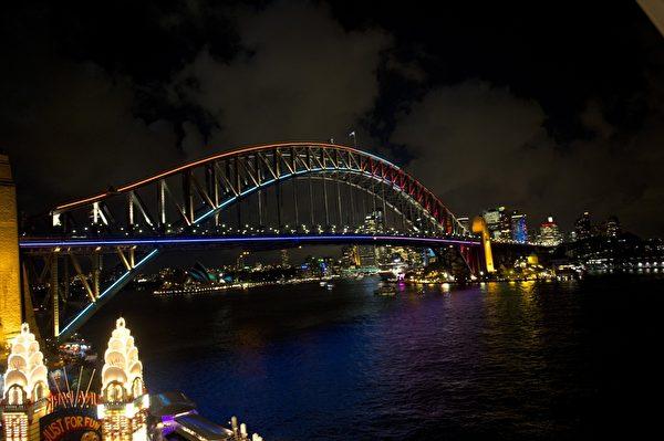 """2013年5月24日,""""雪梨艺术节""""(Vivid Sydney)登场,澳洲雪梨大桥也被上色,与港湾中的雪梨歌剧院交相映照。(SAEED KHAN/AFP)"""