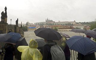中欧近日持续豪雨,捷克宣布进入紧急状态。图为3日在夫塔瓦河畔目睹暴雨中的布拉格的游客。(MICHAL CIZEK/AFP/Getty Images)