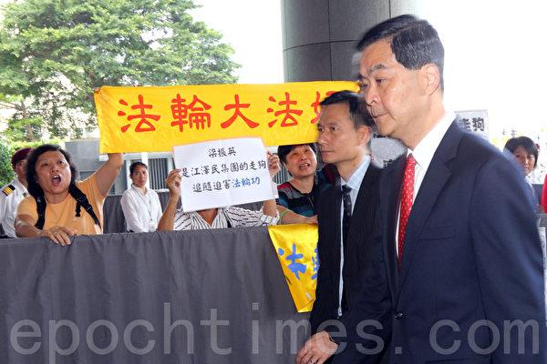 5月29日,4名法輪功學員在香港行政會議早上召開之際,到特首辦外抗議。法輪功學員張開「法輪大法好」橫幅,還高舉新造的「江澤民集團的走狗梁振英追隨迫害法輪功」展板。(攝影:潘在殊/大紀元)
