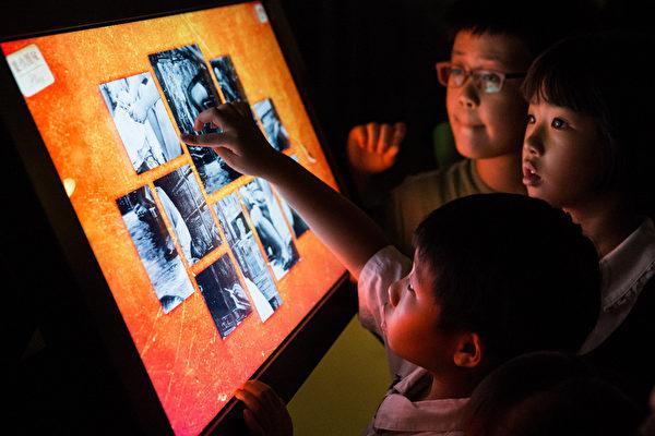 「新唐人穿越時空互動大展」12日於台北花博爭艷館開展,小朋友開心體驗「油畫作品互動光雕拼圖」。(攝影:陳柏州/大紀元)