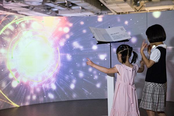 「新唐人穿越時空互動大展」12日於台北花博爭艷館開展,小朋友開心體驗「古典名曲視聽覺劇場」,並當起小指揮。(攝影:陳柏州/大紀元)