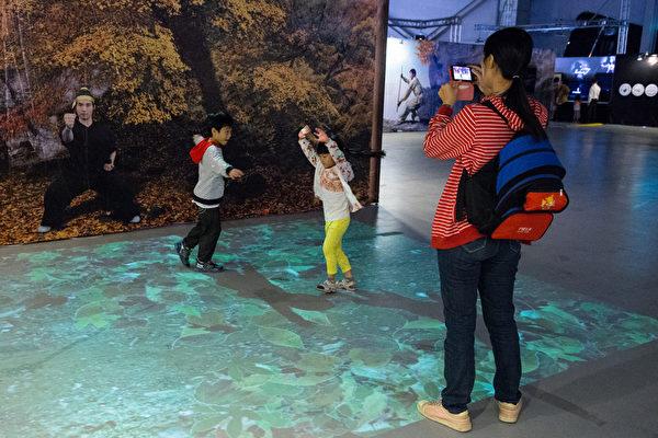 「新唐人穿越時空互動大展」12日於台北花博爭艷館開展,小朋友開心體驗「秋風掃落葉」。(攝影:陳柏州/大紀元)