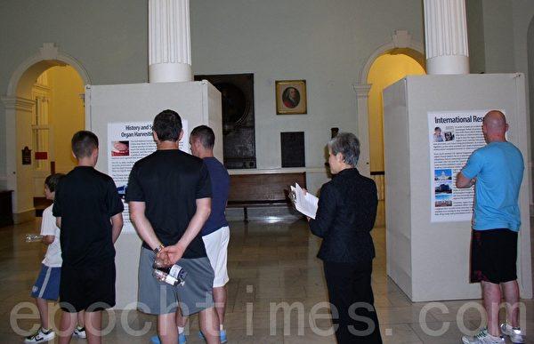 遊客認真閱讀「中共活摘器官圖展」展板。(攝影:秦川/大紀元)