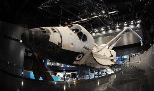 2013年6月7日在佛罗里达州肯尼迪航天中心展厅亚特兰蒂斯号航天飞机有效载荷舱门打开,伸出机械臂。亚特兰蒂斯置于30英尺(9.1米)高处,并以43.21度角倾斜,仿佛绕地球运行(AFP PHOTO/Bruce Weaver)