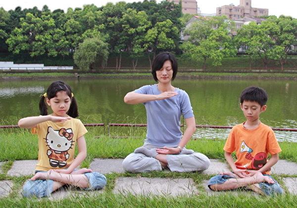 研究发现,打坐可增加善心,去掉私念。妈妈与小孩在湖畔打坐炼功(摄影: 梁淑菁 / 大纪元)