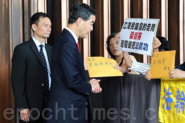 """5月28日早上,4名法轮功学员在香港行政会议召开之前,到特首办外抗议。法轮功学员高举""""江泽民集团的走狗梁振英追随迫害法轮功""""展板,梁振英当时怔住了。随后,梁振英的连串报复行动开始。(摄影:潘在殊/大纪元)殊/大纪元)"""